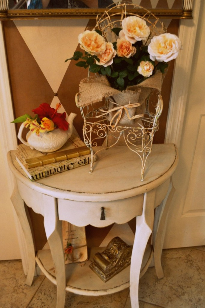 entry table with teapot full of flowers, roses in burlap on an antiqued chair