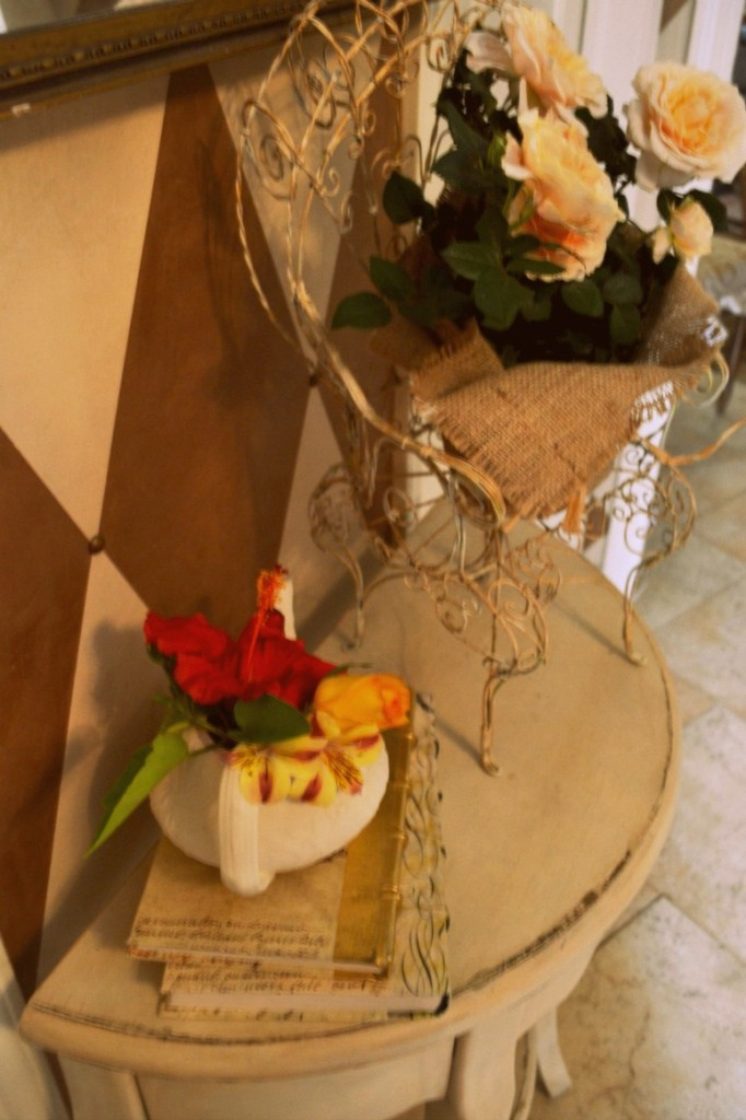 entry table with teapot full of flowers and roses in burlap