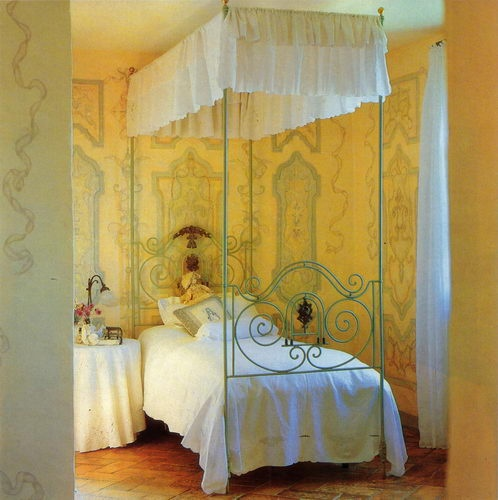 Old fashioned bedroom with yellow walls and decorative painting