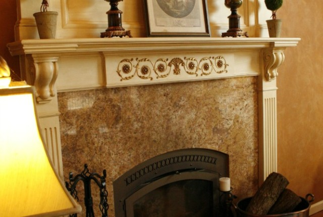 A simply decorated mantle in a great room. Gold leafing and antiquing a fireplace mantle
