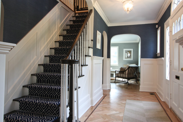 Navy blue entryway with white wainscoting