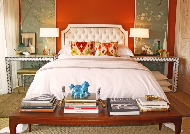 rich orange bedroom, white bedspread, ikat pillows, tufted white headboard, decorative panels as artwork