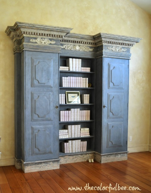 a blue gray Tara Shaw bookcase in a beautiful room