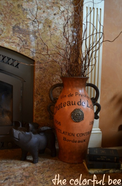 an orange French vase on a fireplace hearth