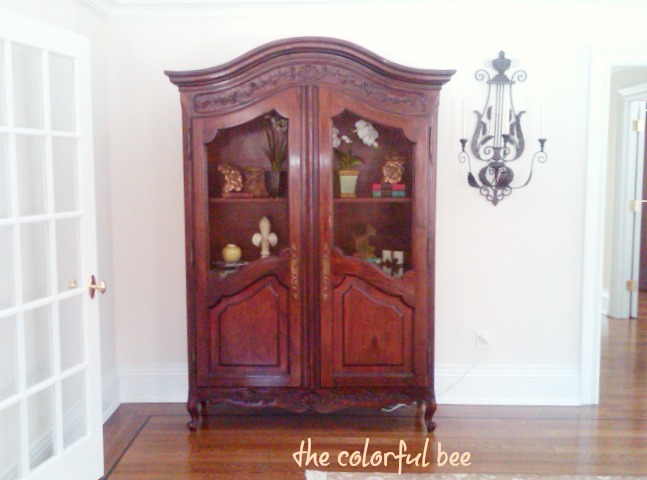 antique armoire in a staged master bedroom