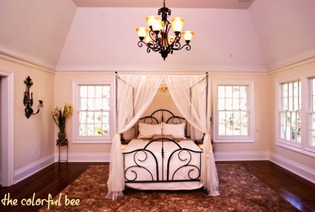 canopy bed with gauze drapes in a staged bedroom