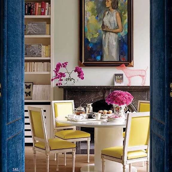 upholstered blue door and art in a white room